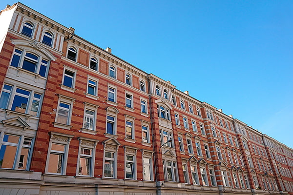 Renditeobjekte Reihenhäuser Altbaustil rot-orange mit blauem Himmel